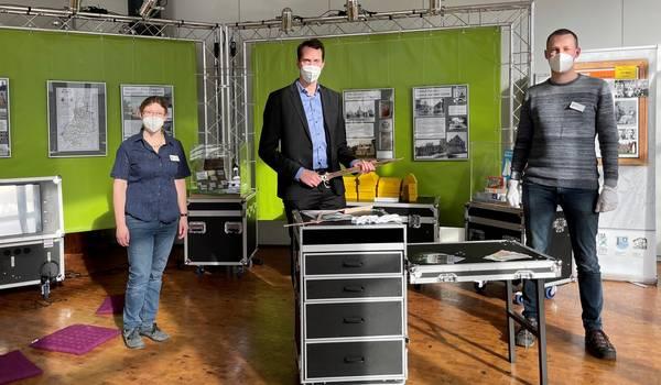 Landrat Dr. Steffen Burchhardt (Mitte), Antonia Beran, Leiterin des Kreismuseums, und Museumspädagoge Moritz Weber präsentieren die Museumskoffer